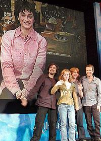 (後ろ)スクリーンに登場したダニエル・ラドクリフ (前列左より)会場で手を振るキュアロン監督、 エマ、ルパート、デビッド・ヘイマン「ハリー・ポッターとアズカバンの囚人」