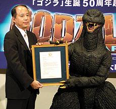 認定証を掲げるゴジラと富山プロデューサー「ゴジラ FINAL WARS」