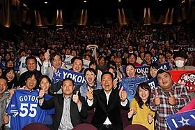 ファンとともに記念撮影を行った 中畑清監督(中央右)と後藤武敏選手「ダグアウトの向こう 今を生きるということ。」