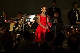 赤のドレスを着て大勢の前で「オポチュニティ」を歌うアニー「アニー」