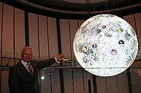 お台場・日本科学未来館の球体ディスプレイ「ジオコスモス」(宇宙から見た地球や月などを映し出す)を前にした、バズ・オルドリン氏。表示されているアポロ11号着陸地点を指す