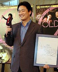 右手に主人公のフィギュアを、 左手にカンヌの賞状を持つ パク・チャヌク監督「オールド・ボーイ」
