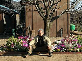 険しい表情で座り込む夏八木勲扮する小野泰彦「希望の国」