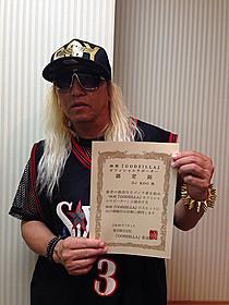 「GODZILLA」オフィシャルサポーターの 認定証を掲げるDJ KOO「ゴジラ」