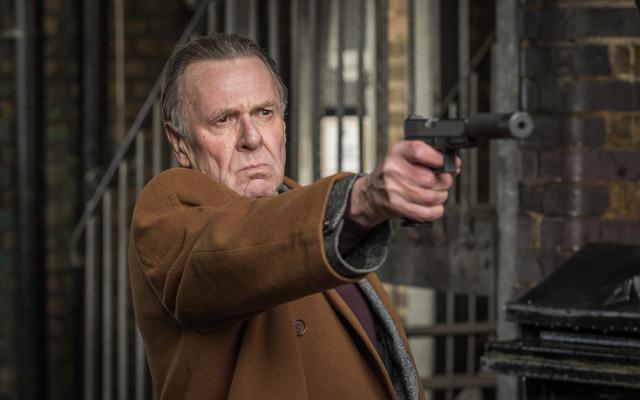 落ちぶれた殺し屋役のトム・ウィルキンソン