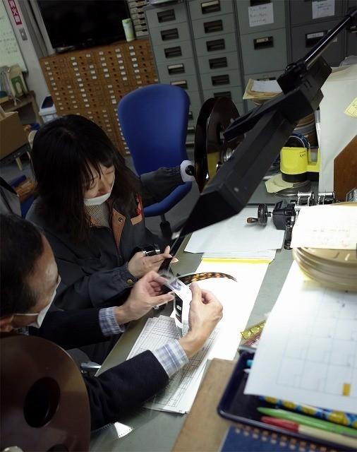 フィルムを1コマずつ確認しながらタイミングを行う鈴木さんと小泉さん