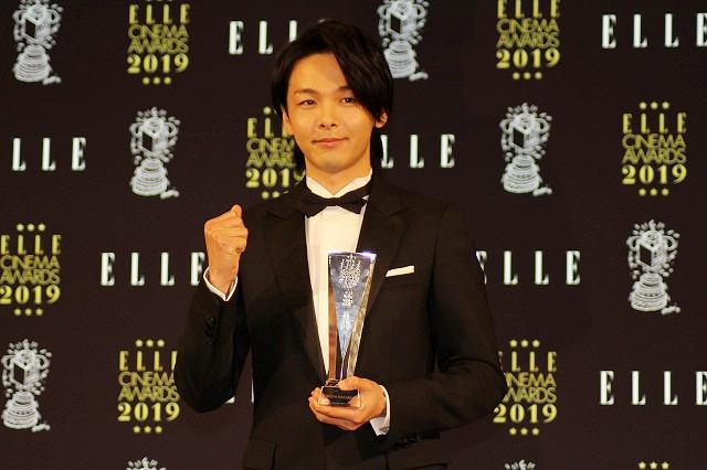 「エル メン賞」のトロフィーを受け取り、ガッツポーズの中村倫也