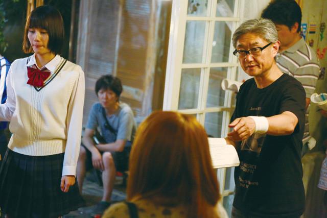 撮影現場で演出中の堤監督(右)