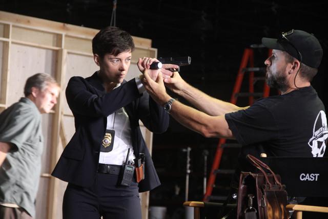 海軍出身の監督(右)が銃の構えも直接指導!