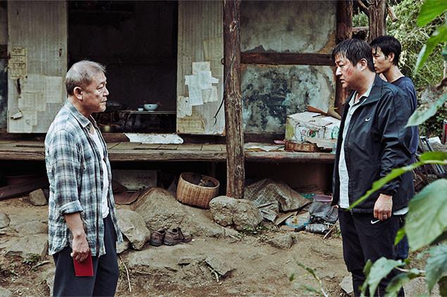村の警官ジョング(右)は、村はずれに住む謎の日本人と対じするが……